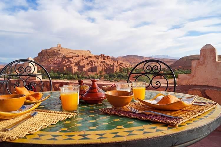 Tafel met ontbijt en sinaasappelsap en bergen