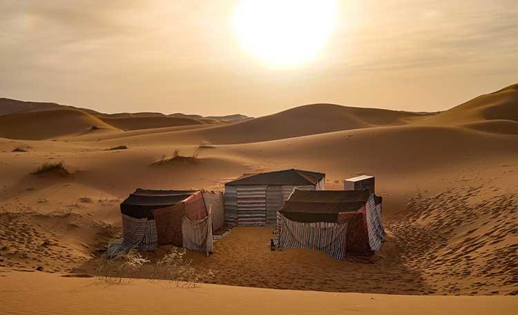 Tenten bij zonsondergang in de woestijn van Marokko