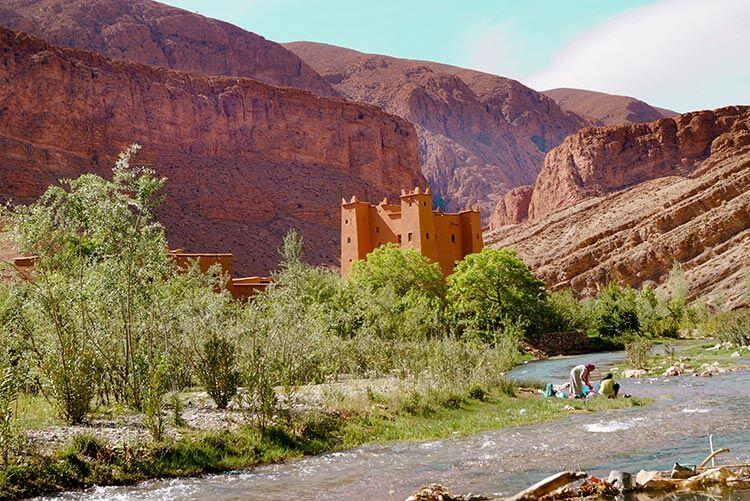 Vrouwen bij rivier kasteel en bergen